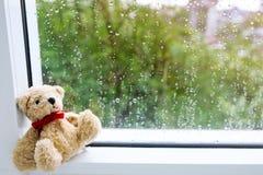 Teddy Bear con el arco rojo de la cinta se sienta tristemente por la ventana y el exterior, él el ` s que llueve y frío fotos de archivo