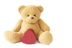 Teddy Bear con un corazón en el fondo blanco Imagen de archivo
