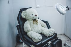 Teddy bear in cosmetic chair, lamp magnifier for beautician , beautician workplace, black chair beauticia stock photography