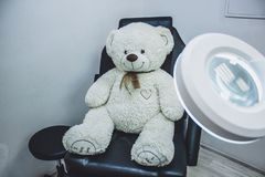 Teddy bear in cosmetic chair, lamp magnifier for beautician , beautician workplace, black chair beauticia stock photos