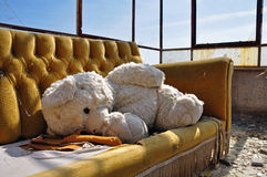 Teddy bear and couch in abandoned building Stock Photo