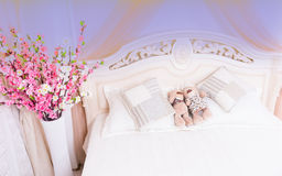 Teddy Bear Couple Snuggling on Romantic Bed. High Angle View of Romantic Pink and White Bouquet of Flowers Beside Bed with Male and Female Couple Teddy Bears Stock Image
