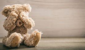 Teddy bear covering eyes stock image
