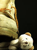 Teddy bear crushed by a heavy, old military boot. Stock Photography