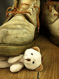 Teddy bear crushed by a heavy, old military boot. Stock Photos