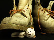 Teddy bear crushed by a heavy, old military boot. Royalty Free Stock Photo