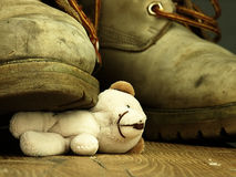 Teddy bear crushed by a heavy, old military boot. Royalty Free Stock Image