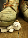 Teddy bear crushed by a heavy, old military boot. Royalty Free Stock Images