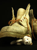 Teddy bear crushed by a heavy, old military boot. Stock Images