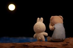 Teddy bear crying and rabbit doll giving consolation royalty free stock images