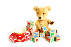 Teddy bear, cup, plate and box of bricks isolated on white Stock Photo