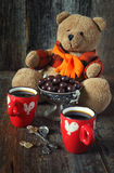 Teddy bear,  cups of coffee  and chocolate drops. Teddy bear, two cups of coffee  and chocolate drops. Toned image Royalty Free Stock Image