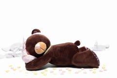 Teddy Bear, der ein Herz auf weißem Hintergrund hält Stockbild