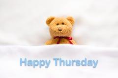 Teddy Bear, der im weißen Bett mit Mitteilung glücklicher Donnerstag liegt stockfotos