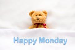 Teddy Bear, der im weißen Bett mit Mitteilung u. x22 liegt; Glücklicher Montag u. x22; lizenzfreies stockbild