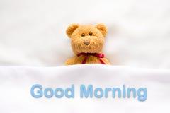 Teddy Bear, der im weißen Bett mit Mitteilung u. x22 liegt; Gutenmorgen u. x22; Lizenzfreies Stockfoto