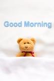 Teddy Bear, der im weißen Bett mit Mitteilung u. x22 liegt; Gutenmorgen u. x22; Stockfotografie
