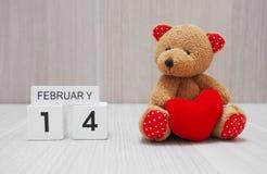 Teddy Bear, der mit rotem Herzen sitzt Stockfotografie