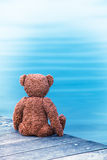 Teddy Bear with a Desire. Back of a brown teddy bear sitting alone at wooden planks of a pier at the sea Royalty Free Stock Photos