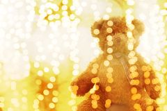 Teddy bear doll in Lighting line bokeh gold bright for Christmas or happy new year Background, Bear in glitter Gold yellow. The Teddy bear doll in Lighting line royalty free stock images