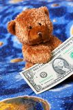 Teddy bear and dollars Stock Photos