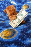 Teddy bear and dollars Stock Images