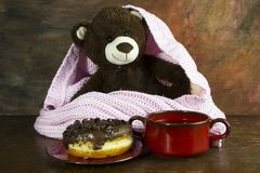 Teddy bear, donuts, and tea on wooden table Royalty Free Stock Photography