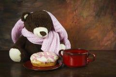 Teddy bear, donuts, and tea on wooden table Stock Photos