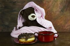 Teddy bear, donuts, and tea on wooden table Royalty Free Stock Photo