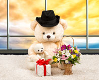 Teddy bear dressed in a hat,a surprise gift and basket of flowers at sunset .The panoramic Windows. Plush stuffed bear,gifts,surprises.Gifts for the holiday stock images