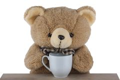 Teddy bear drinking tea isolated on white background. Teddy bear drinking tea on the table isolated on white background royalty free stock photos