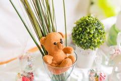 Teddy Bear in einer Glasschale mit grünem und weißem Geburtstags-Tabellen-De stockbild