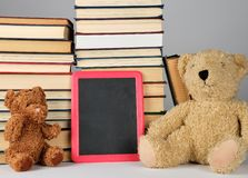 Teddy bear and empty black board in red frame on the background of pile of books. Brown teddy bear and empty black board in red frame on the background of pile royalty free stock photo