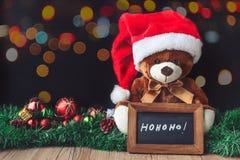 Teddy Bear et Santa Hat dans Noël avec le conseil et la tache floue noirs Photo stock