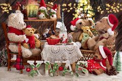 Teddy bear family at christmas time with milk and cookies. Teddy bear family in santa hats sitting at home on vintage style wicker sofa and chair by the table Stock Image