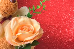 Teddy bear with flowers in valentines day on red glitter bokeh lights Blurred abstract background Stock Images