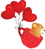 Teddy bear flying in red cup with heart balloons Stock Photos