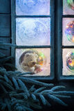 Teddy bear in frozen window for Christmas with tree and lights Stock Photo
