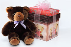Teddy bear with gift box. Cute brown teddy sitting next to a beautifully wrapped present box, waiting to be a gift to someone special Stock Photography