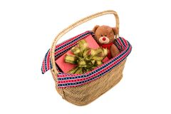 Teddy bear with gift box in basket. Teddy bear with red gift box in wicker basket Stock Photo
