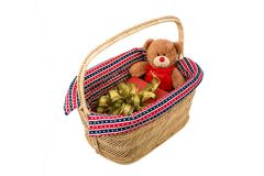 Teddy bear with  gift box in basket. Teddy bear with red gift box in wicker basket Royalty Free Stock Images