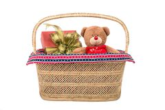 Teddy bear with gift box in basket. Teddy bear toy with red gift box in wicker basket on white background Stock Images
