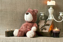 Teddy bear and gift box with candles on sack background. Teddy bear and gift box with candles on sack/burlap background Royalty Free Stock Photo