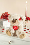 Valentine or birthday surprise teddy bear and gift. Valentine or birthday teddy bear, red hearts, gift box and red candle on background. Gifts Royalty Free Stock Images
