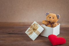 Teddy bear in gift box and red heart on wooden background Royalty Free Stock Photo
