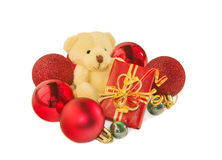 Teddy bear with gift and Christmas baubles on white. Royalty Free Stock Images