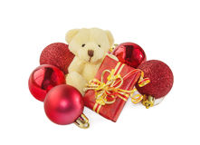 Teddy bear with gift and red Christmas balls on white. Royalty Free Stock Photo