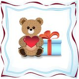 Teddy bear and a gift. Teddy bear with red heart and a gift nearby Stock Photos