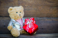 Teddy bear and gift on wooden background Royalty Free Stock Photography