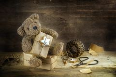 Teddy bear on a giftbox and shows a Christmas gift, dark wooden background, copy space. Teddy bear sits on a giftbox and shows his wrapped Christmas gift, kraft royalty free stock photos